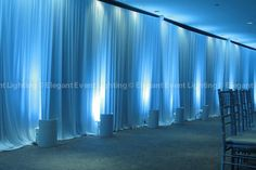 We adorned the walls with gorgeous, white floor-to-ceiling draping.  Therese  Jeff chose a crisp, blue uplighting color which accented the elegant pleated design and enhanced the winter theme of their wedding.