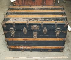 VINTAGE STEAMER TRUNK WITH LEATHER HANDLES (ONE IS BROKEN). THE TRUNK HAS OAK SLATS AND METAL HARDWARE. MEASURES 21 INCHES TALL, 32 INCHES WIDE AND 18 INCHES DEEP.