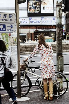 Woman in long-sleeved flowered dress & tan pumps with a bike.