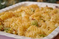 300 g di cavolfiore bianco 300 g di broccolo romanesco 1 cipolla bionda 2 cucchiai di olio extravergine di oliva sale 320 g di pasta 300 ml di besciamella 20 g di burro 30 g di Parmigiano Reggiano