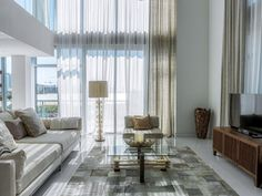 A wash of gold and silver add glitz and glamour to this sophisticated living room. The air of luxury is enhanced through the choice of materials: crystal, metal, glass and suede.