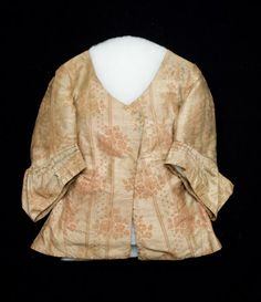 1760-1790, Jacket - Silk damask, cream ground with design of floral sprays. Narrow stripes of green and blue warp. Silk late 1750's? Lined throughout unbleached loose-woven cotton. Hip length. Low, round neck, centre front opening. Front cut plain. Gusset in skirt at side seam. Back shaped with 4 panels. Box pleated gusset centre back to give a wide flare to skirt. Sleeves set in, wide, elbow length with deep wide cuff. Sleeves in earlier fashion. shown in J. A. and N.B., Inv. no. 1348744