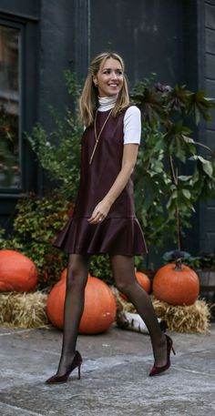 Burgundy faux leather drop waist shift dress with flutter ruffle hem layered over white ribbed short sleeve turtleneck, gold long lariat necklace and burgundy red velvet classic pointy toe pumps.
