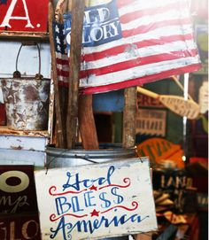 These painted wooden signs and flags at the Berries in the Meadow booth would be ideal for Fourth of July decorating.