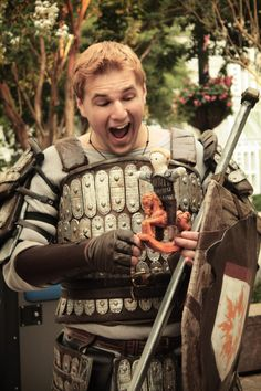 A cosplay of Alistair from Dragon Age Origins, playing with a doll of himself and a little horsey. That is one of he most fantastic look-alikes I have seen. And his costume is so well made!!!