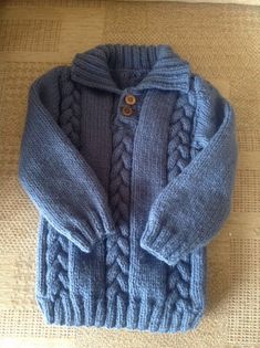 Handknitted boys cable Sweater in a lovely petrol blue. Knitted with a collar and two-button opening at neck to allow ease of putting on. Approximate size: To fit age (approx) months Chest: inches) Overall length: inches) Sleeve length: inches) Knitted in Knitted Baby Cardigan, Cable Sweater, Knitted Hats, Aran Weight Yarn, Handmade Shop, Handmade Gifts, Unique Gifts, Love Blue, Knit Fashion