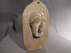 """carved wood panel with female kifwebe (mask) from the Songye people, settled in DR Congo. Material: Wood and pigments. Dimensions: 11.5"""" ( 29 cm) in height."""
