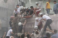 Syrian rescue workers and citizens evacuate people from a building following a reported barrel bomb attack by Syrian government forces on the central al-Fardous rebel-held neighborhood in the northern Syrian city of Aleppo. June 9, 2015.