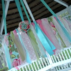 For a girly room. Hula hoop + ribbon + fabric strips + flowers = easy chandelier.  I could use this in the baby shower but do it in he baby's room colors so that she could use it in the room!!