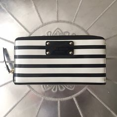 Kate Spade Zip Around Wallet Clutch This is a slightly used zip around wallet by Kate Spade!! It's so very cute! It's patent leather, shiny and black and white strips with polka dot detailing inside. Has one slim pocket on the outside, 12 credit card slots inside, a zip coin pocket inside and tons of other slots and spaces!! It can even hold an iPhone! So can work well as a clutch too! The outside does show slight wear from the one month that I used it. No color changes or anything, just…