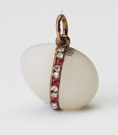 Fabergé miniature Easter egg pendant of white quartzite set with rose diamond and ruby band at a diagonal across the body, from which hangs gold ring. Mark of Henrik Wigström, 1917. Probably acquired by Queen Alexandra.