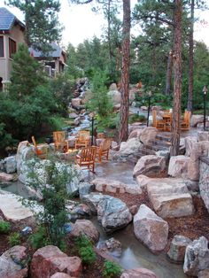 An outdoor walkway is surrounded by large stone boulders and woodsy landscaping to create the ideal rustic backyard. Several seating areas, including one with a fire pit, feature wooden furniture that is perfect for relaxing and enjoying the nearby waterfall.