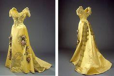 Lang aftenkjole i stærkt gul silke. kjolen er besat med broderier og dekoreret med ranker af kunstige, lyserøde roser.