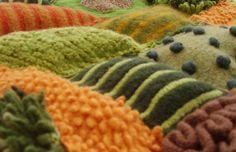 Patchwork fields, detail by Lou Baker   Hand knit felt fields appliquéd onto machine knit felt and stuffed