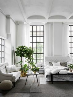 Luxurious and cozy all white bedroom with from floor to ceiling windows
