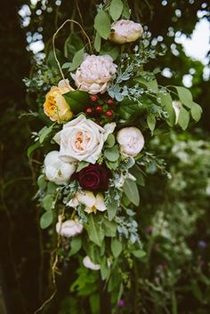 A wedding arch adorned with leafy greenery, peonies, roses, and rose hips | Photo by E + E Photography
