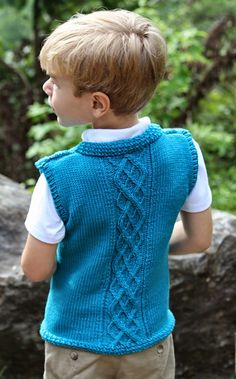 This suave and sophisticated sweater vest gives an intelligent air to the child who wears it. The solid color highlights the intricacies of the diamond cable panels on the front and the cabled argyle panel in the back.