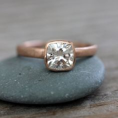Moissanite and Rose Gold Engagement Ring. So unique. So shiny. I'm in love. Just add a matching rose gold band (or two--one on each side for a stacked look!)  Details: Cushion Cut Moissanite Engagement Ring in14k Rose Gold, Solitaire Cushion Cut Gemstone Ring by onegarnetgirl on etsy.com