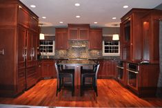 Cherry cabinets are topped with black granite counters. The backsplash is made of glass tiles. The floors are made of Angico wood. New Kitchen Cabinets, Kitchen Tiles, Kitchen Flooring, Kitchen Design, Cherry Wood Kitchens, Cherry Kitchen, Cherry Cabinets, Birch Cabinets, Mission Style Kitchens