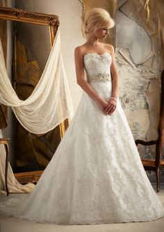 With the heavenly sounds of music and the fragrance of the beautiful flowers, you will add to the ceremony when you enter wearing Mori Lee 1913 wedding dress made of Alencon lace and spectacular trim of sparkling beads. You just stole the attention of every guest as you gracefully walk to the altar in this A line gown. The strapless neckline whispers opulence and so does the beaded waist band that encircles the gown. #timelesstreasure