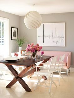 I love the contrast between the pink settee, wood table and white chairs.  Also, the wall color is so soothing.
