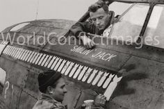 """B-17 """"Knockout Dropper"""" of the 303rd Bomb Group at Molesworth, England. This photograph captures the crew chief Sgt. Stanley Jacobs painting on the 50th mission bomb while pilot John P. Manning looks on. Flying out of Molesworth with the 359th Bomb Squadron, this aircraft was the first in the Eight AAF to complete 50 and then 75 missions. The """"Knockout Dropper"""" also participated in the disastrous Schweinfurt raid and survived."""