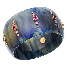 """""""Glenda"""" marbled blue, translucent vintage bakelite bangle with circular-cut pink sapphire and rubelite accents mounted in 18k yellow gold settings. Pink sapphires weighing 3.24 total carats and rubelites weighing 4.14 total carats. 2.5"""" approximate interior diameter. Handmade in the artist's Brooklyn workshop. Designed by Mark Davis."""
