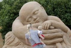 A woman carries a child as they look at a sand sculpture creation by Liga Zarina at the Magic Sand Riga festival in Riga July 5, 2011. (Xinhua/Reuters Photo)
