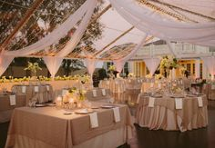 Beautiful use of swag and lighting along with a tent frame to create a magical space!  See these other 9 Ways to Light Your Reception.