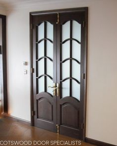 A pair of tall glazed internal double doors installed into a home in London. Our carpenters installed these doors into a new sturdy frame. These internal double doors have been glazed with satin etched obscure glass to offer some privacy to the room while also letting in some light. The glass has a decorative design with arched panels. The doors have been stained with a dark oak wood finish. We fitted this door with polished brass furniture.