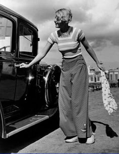 Woman wearing a striped t-shirt and wide-legged trousers with sail boat appliqué at ankle, c. 1930s.