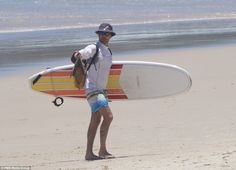 Prince Frederik walks a surfboard off Byron Bay beach after the Royal family enjoyed Boxing Day during their holiday