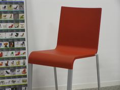 Vier rode Vitra Maarten van Severen 03 stoelen.