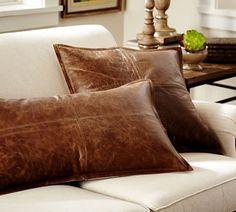 Thinking about leather pillows (accents for the occasional chairs in the great room) like the rectangular one shown.