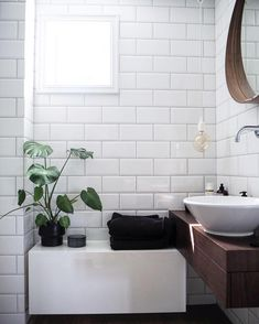 Simple white Metro tiles look great with wooden accessories and some greenery