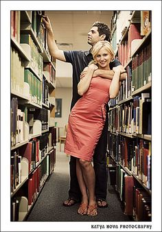 """""""Library engagement photo.""""  At first glance it looks like he's got her in a chokehold. Upon second glance, you notice how he is more interested in books than in her. I'm one of the biggest bibliophiles you'll ever meet, but nothing about this picture says """"we're happily engaged!"""" to me."""