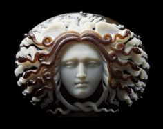 Sardonyx cameo head of the Medusa facing front, eyes cast downwards, mouth pursed in a bitter expression, hair standing out stiffly parallel with the wings at the top of the head. The oval face is framed within five pairs of snakes coiled into spirals terminating in heads hissing outwards amidst the locks of heir: two tails are knotted beneath the chin. Signed PISTRUCCI, Benedetto Pistrucci in 1844. Formerly Esmerian Collection.