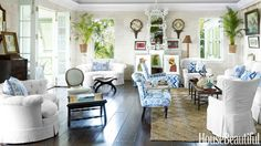 Inspired by 18th-century Caribbean plantations, the great room in designer Amanda Lindroth's Lyford Cay, Bahamas, house exudes a gracious ease. Coral stone walls are a striking counterpoint to the floor, stained to look like mahogany. All seating is vintage. The sofa's white fabric is P. Kaufmann's Slubby Basket, and the chairs are a cotton duck from Norbar; blue-and- white fabrics are Palampore Stripe by Quadrille and Bali Hai by China Seas. Custom coffee and side tables, the Raj Company…