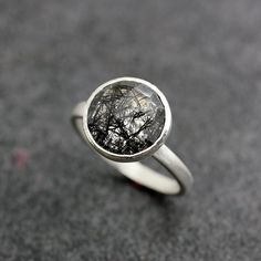 Captivating silver ring with floating black bits within its featured jewel.