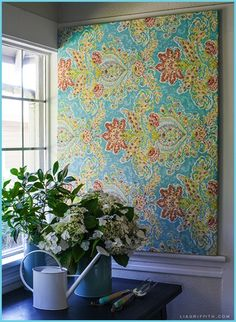 DIY Instant Fabric Art.   10 minute project, and we like the like the sound of that! For the cost of a few yards of fabric, a stretcher and a few staples, you can get your creative juices on