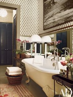 A block-printed fabric designed by Brandolini sheathes the master bathroom; the floor lamp is by Venini | archdigest.com