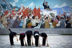 Tuesday, December 1: North Korea:   North Korean schoolgirls holding brooms bow to pay their respects toward a mural which shows the late North Korean leader Kim Il Sung delivering a speech, before sweeping the area surrounding this mural, on Tuesday, Dec. 1, 2015, in Pyongyang.  -    © Wong Maye-E/AP