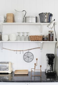 Use a branch and S hooks to hang items in the kitchen. The blog is in Norwegian. :) http://norskeinteriorblogger.no/2015/01/20/mote-moter-interior-hjemme-hos/
