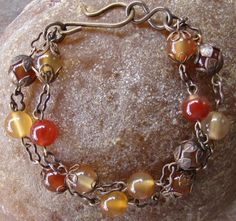 Beautiful beaded bracelet,has 8mm glass beads in tones of oranges and reds,made of 100% natural brass,has different brass 6mm bead caps that cup some of the beads,measures at approx. 7 2/8. ByJenJenWithLove