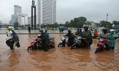 People try to navigate their scooters through floodwaters in Jakarta.