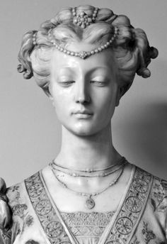 "Large marble bust of a woman in affluent garb. Beaded pearl head dress. Has carved floral decoration and is gilded. Front of bust has ""Matelda"" etched and gilded. No apparent signature. 19th Century. White marble pedestal has a design to top that matches the shape of the base of the bust."