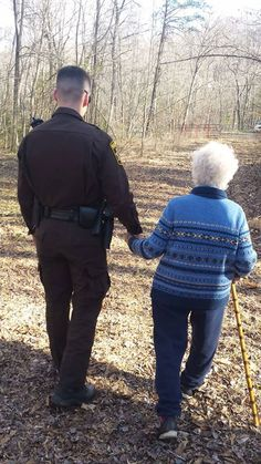 Officer holding older lady's hand
