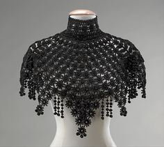 Pelerine This is a nice example of decorative beadwork accessories and garments which were considered high style in the 1880s and 1890s. The pendant points and ball fringe would make a lively, glittering Date: ca. 1890 Culture: American Medium: jet, silk Dimensions: Length at CB: 14 in. (35.6 cm) Credit Line: Brooklyn Museum Costume Collection at The Metropolitan Museum of Art, Gift of the Brooklyn Museum, 2009; Gift of Dr. Clark Burnham in memory of his wife, Matilda Spelman Burnham, 1934