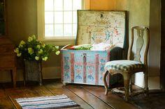 Um raro baú sueco pintado, em um quarto.