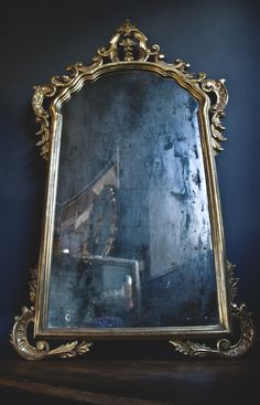 This is a lovely foxed gilt framed wall mirror. It has beautiful wooded details moulded into and arch form with scroll and acanthus detail. The glass has almost a smokey sheen to it and quite a bit of foxing it gives an almost misty grey reflection which is unusual. There has been a repair to the wood details at the top but it is in lovely condition with a deep gold tone to the gilt.